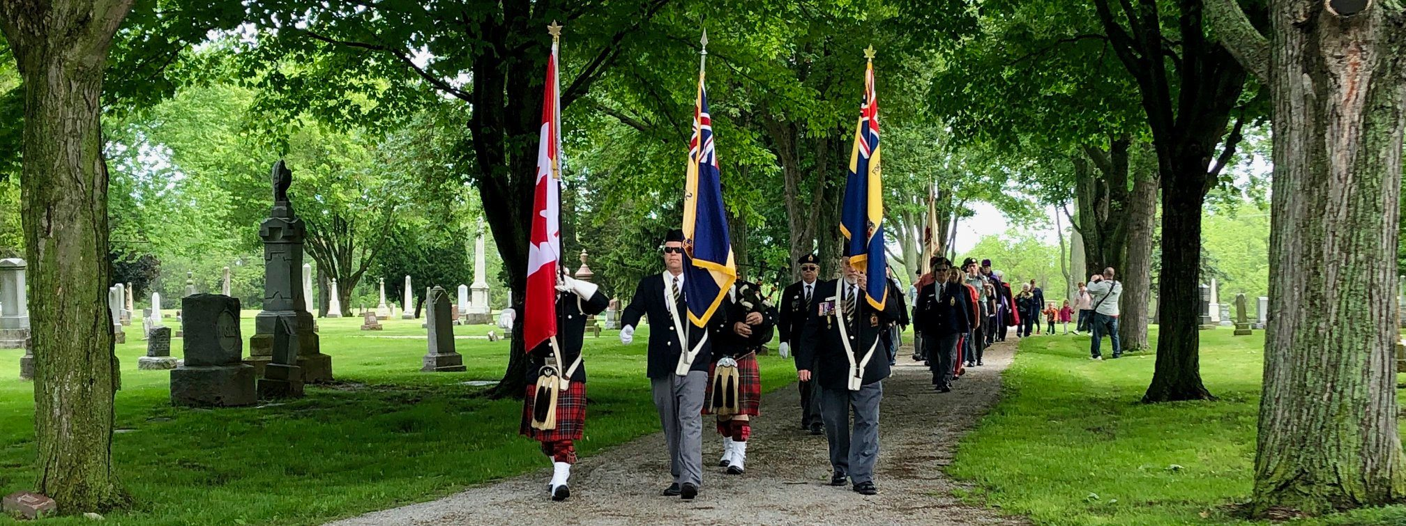 Royal Canadian Legion members march with flags.