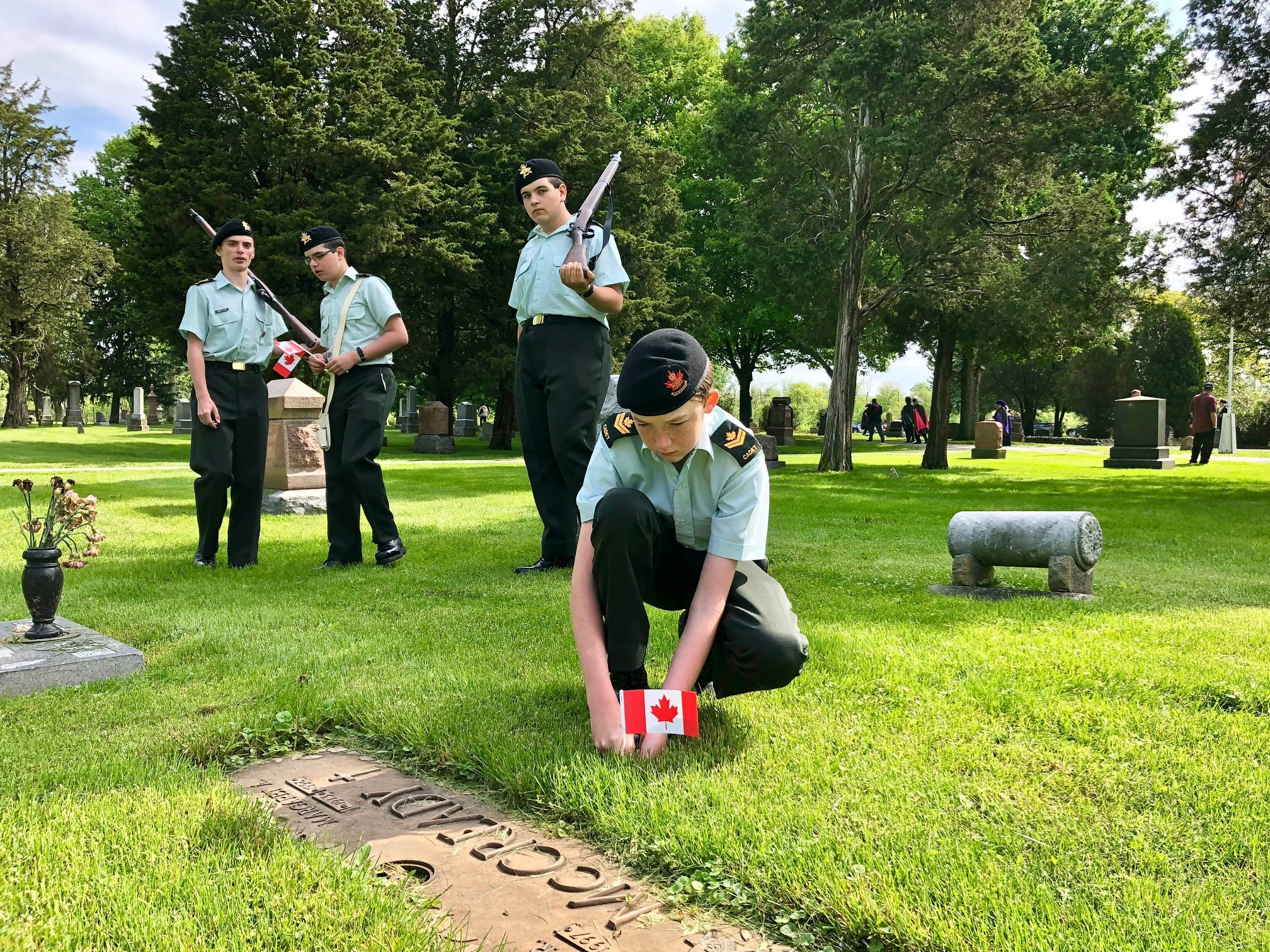 A cadet plants a Canadian flag while three cadets holding rifles look on.