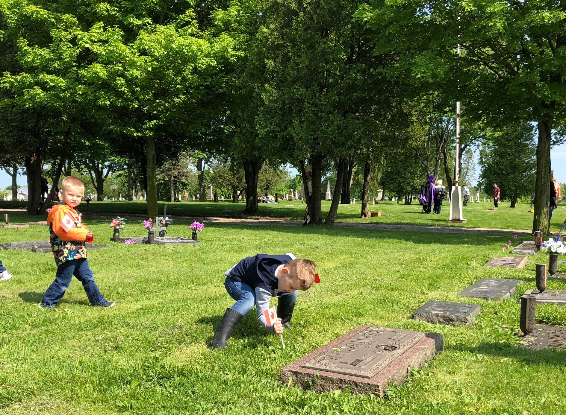 A child plants a flag at a grave marker while another walks with a flag.