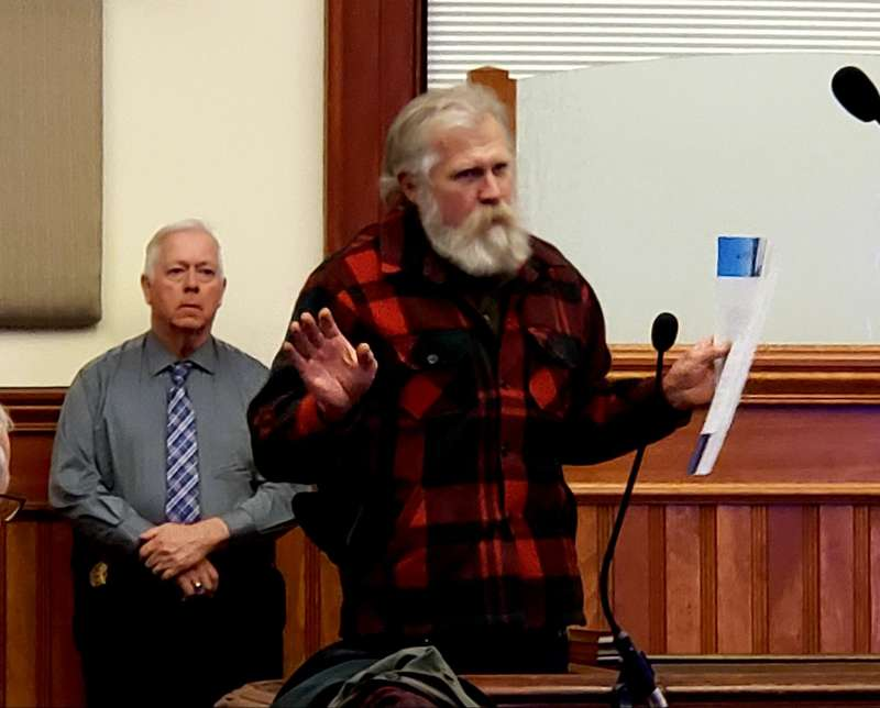 "Washington County Sheriff Barry Curtis looks on as Larry Balchen speaks in opposition to the Downeast Wind project. Balchen showed a wide-angle photo taken from Route 1 to demonstrate how far the towers might be visible on what Balchen called the ""last 100 miles of undeveloped land on the eastern seaboard."" Photo by Sarah Craighead Dedmon"