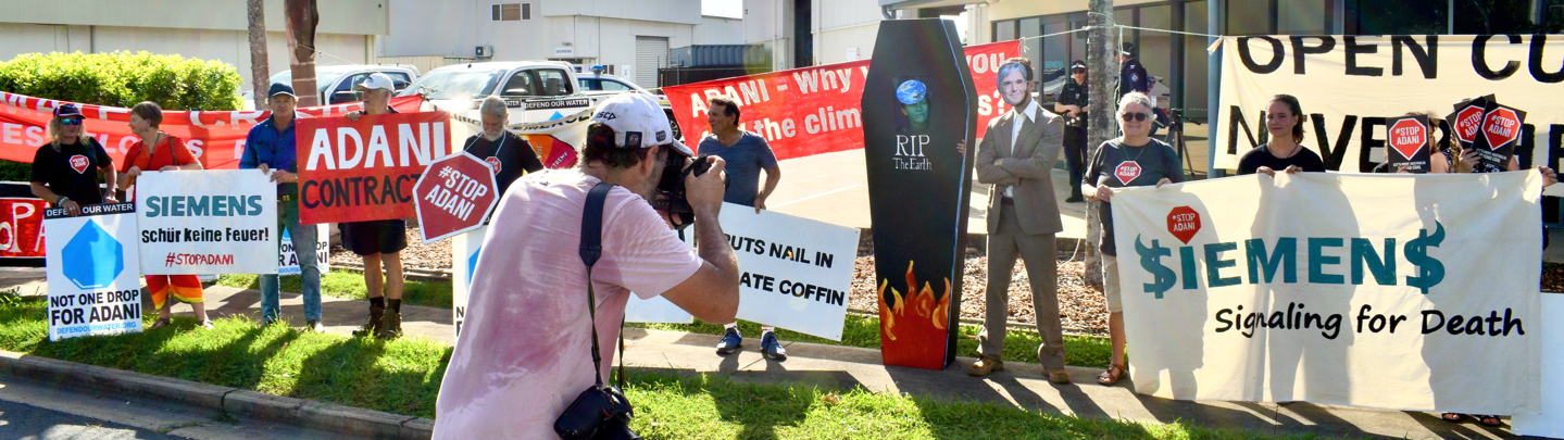 A group of people standing outside the office of Siemens in Mackay holding placards protesting the company's support for the Adani mine
