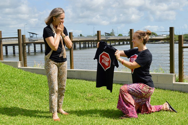 Image: One person presenting another person with a Stop Adani T-Shirt