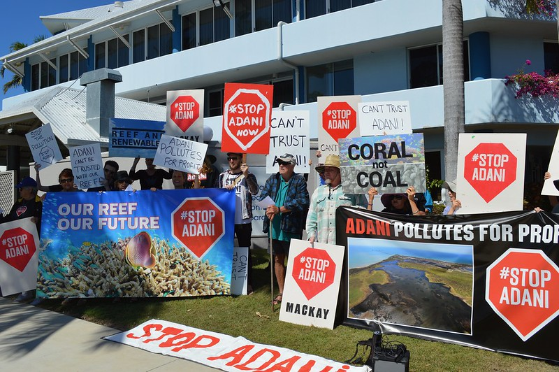 Mackay residents protest the Adani mine holding signs which say Stop Adani, our reef our future, Adani pollutes for profit.