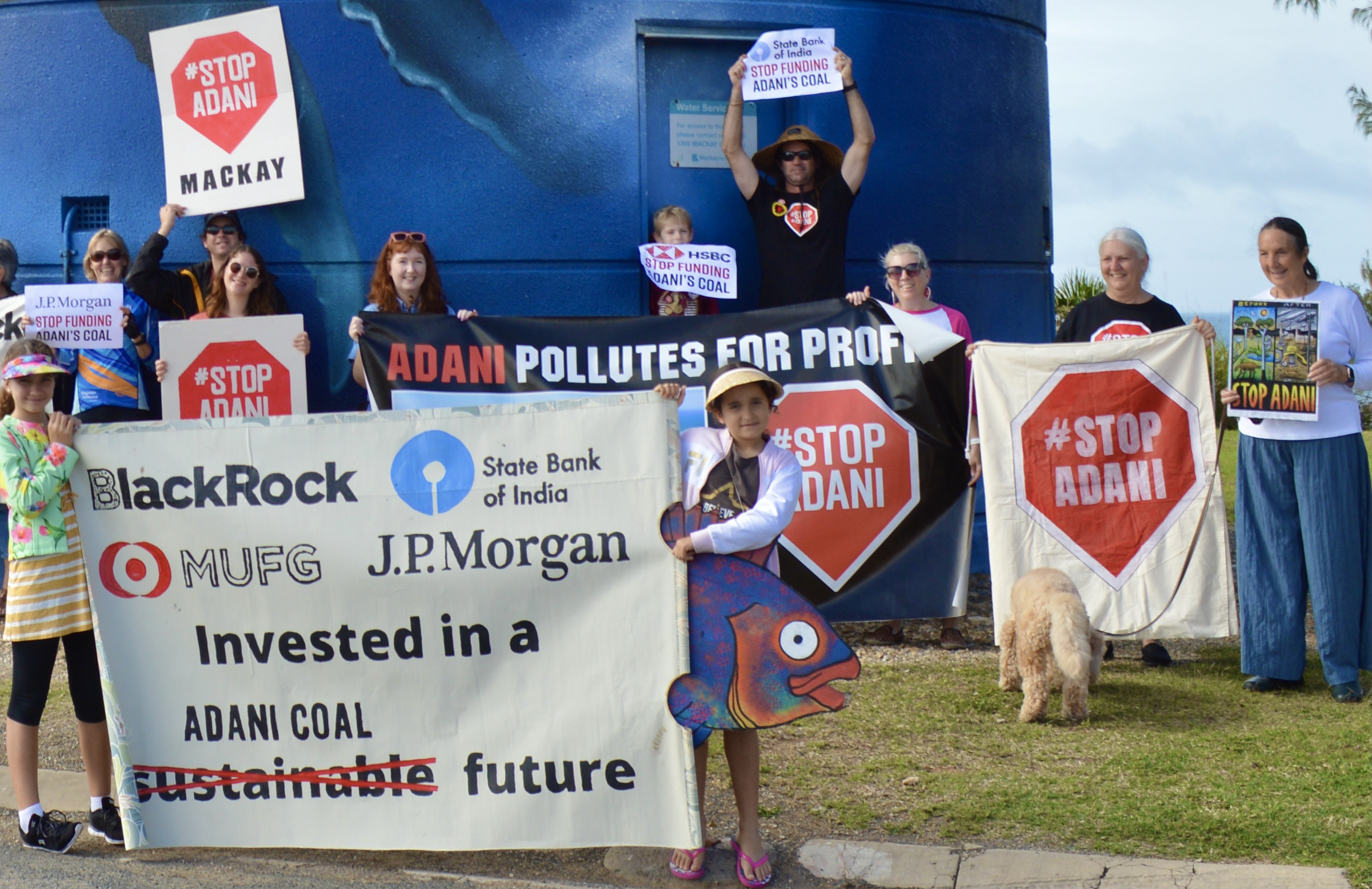 Image: A group of people standing outdoors with a whale mural behind them, holding signs telling Adani investors to stop funding Adani coal