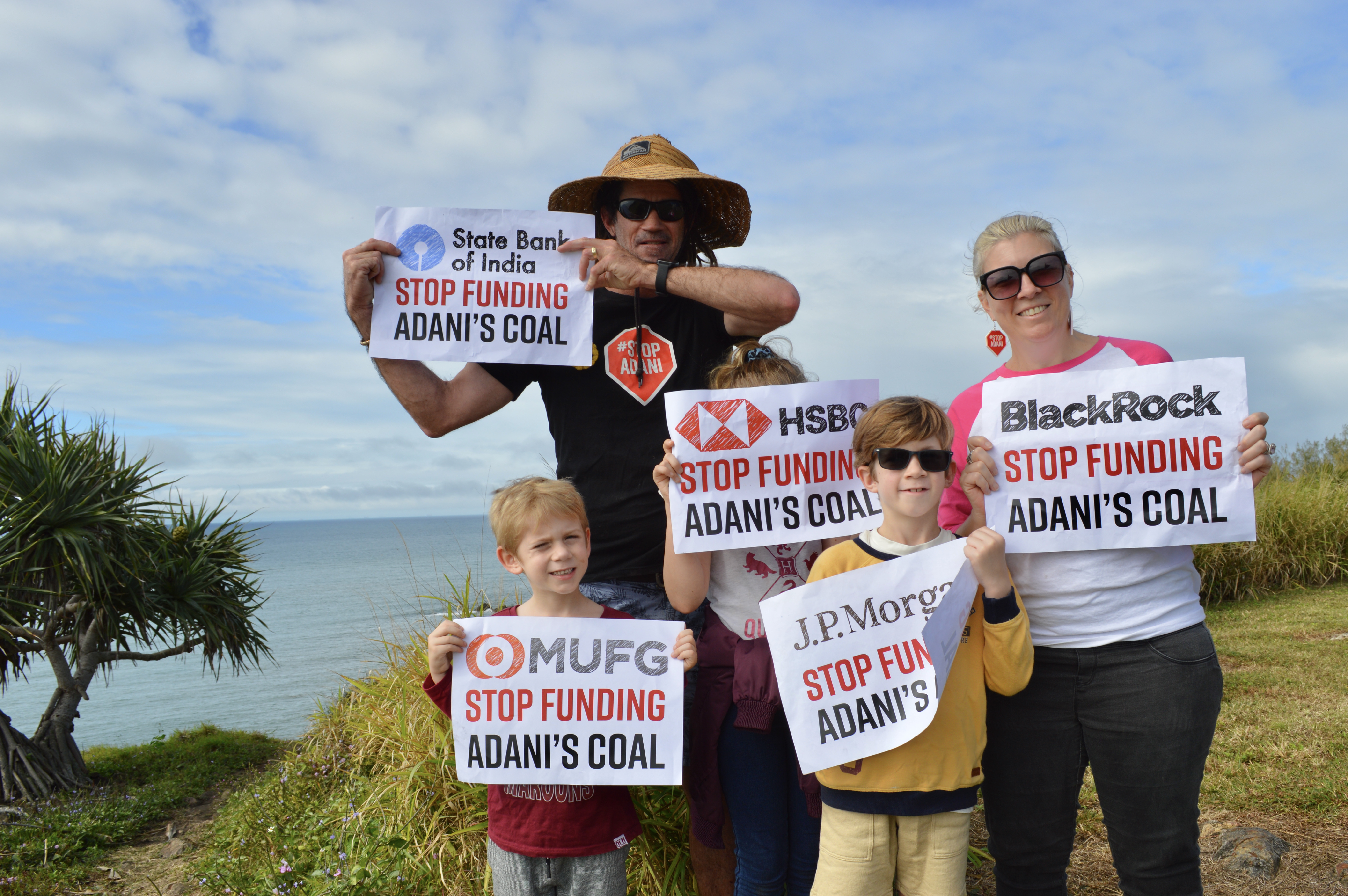 Image: A family standing outdoors with the ocean behind them, holding signs telling Adani investors to stop funding Adani coal