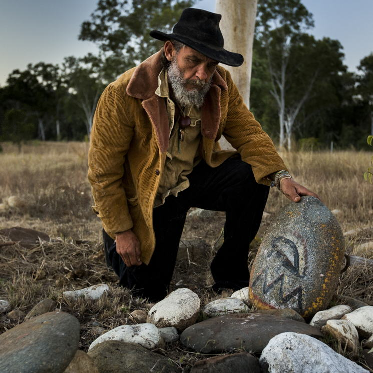 Wiri man, Kenny Dodd, looks down at rocks painted with symbols