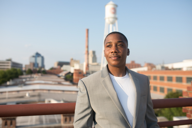 AJ Williams wearing white t-shirt and suit jacket with Durham skyline in background