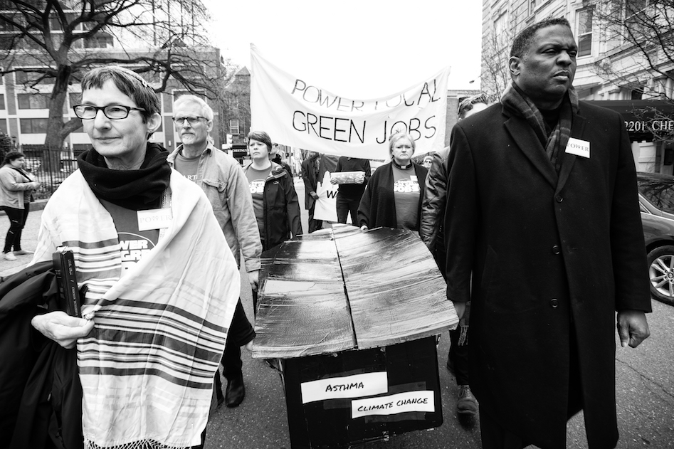 Mourners carrying a coffin of dirty energy suffering.