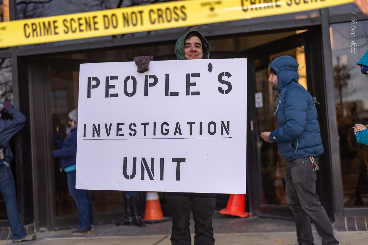 Ben Safran holds a People's Investigation Unit sign in front of crime scene tape at the PECO building.