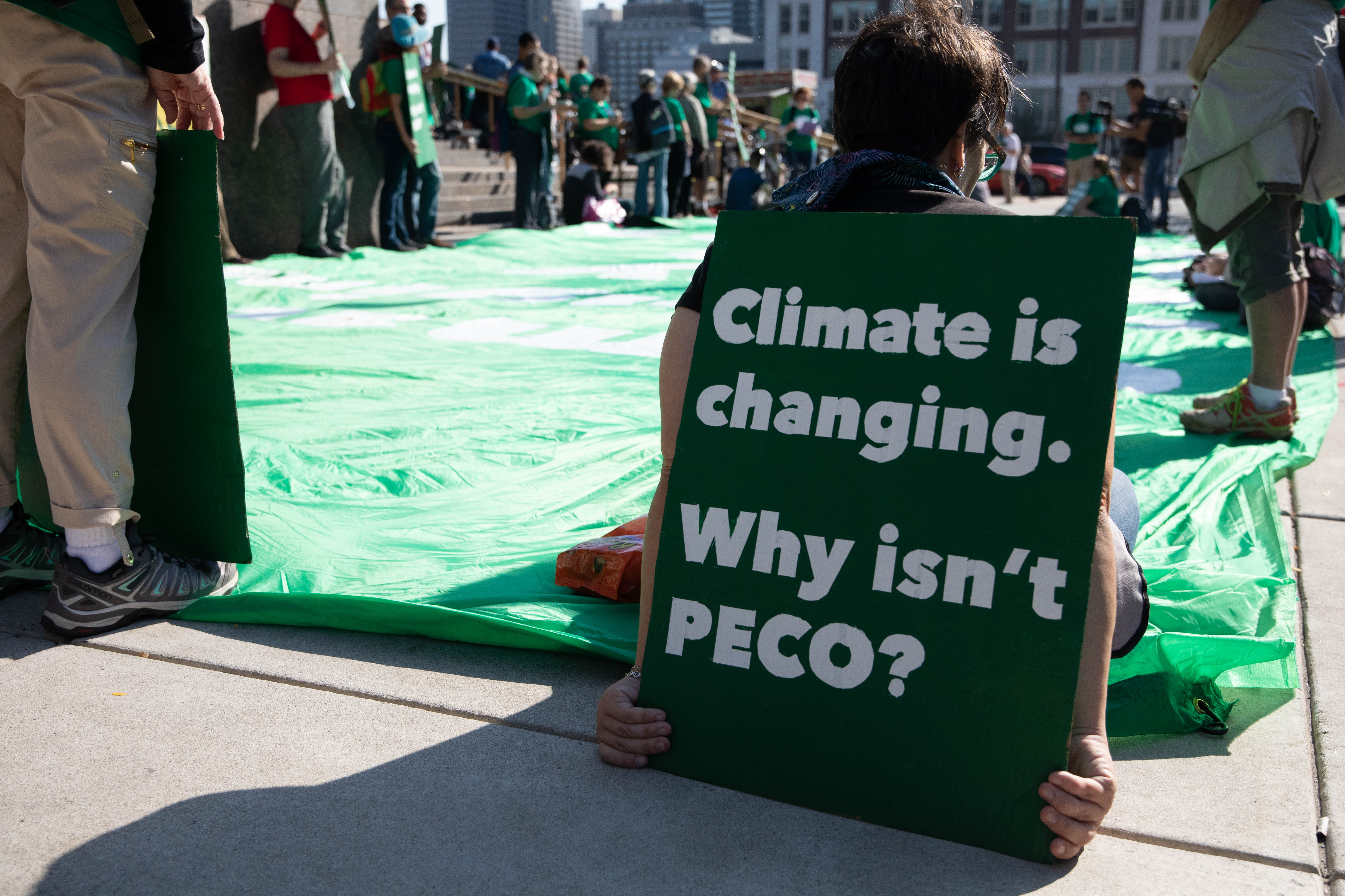 """An activist sits on a huge green banner holding a sign that says """"climate is changing, why isn't PECO?"""""""