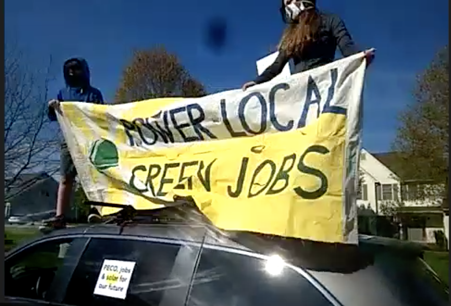 Two EQATers hold a banner that reads Power Local Green Jobs while standing on a car parked across from a large suburban house.