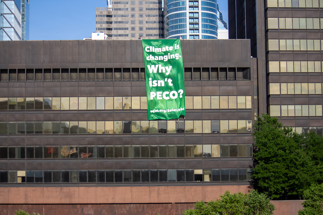 """A brilliant green banner hangs down four stories off of the roof of the PECO building. The banner reads """"Climate is changing, why isn't PECO?"""""""