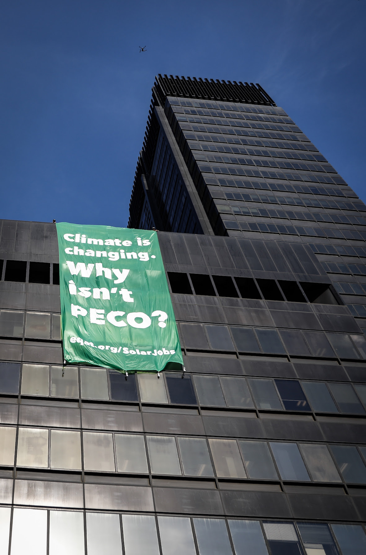 "A brilliant green banner hangs down four stories off the roof of the PECO building. The banner reads ""Climate is changing. Why isn't PECO?"""