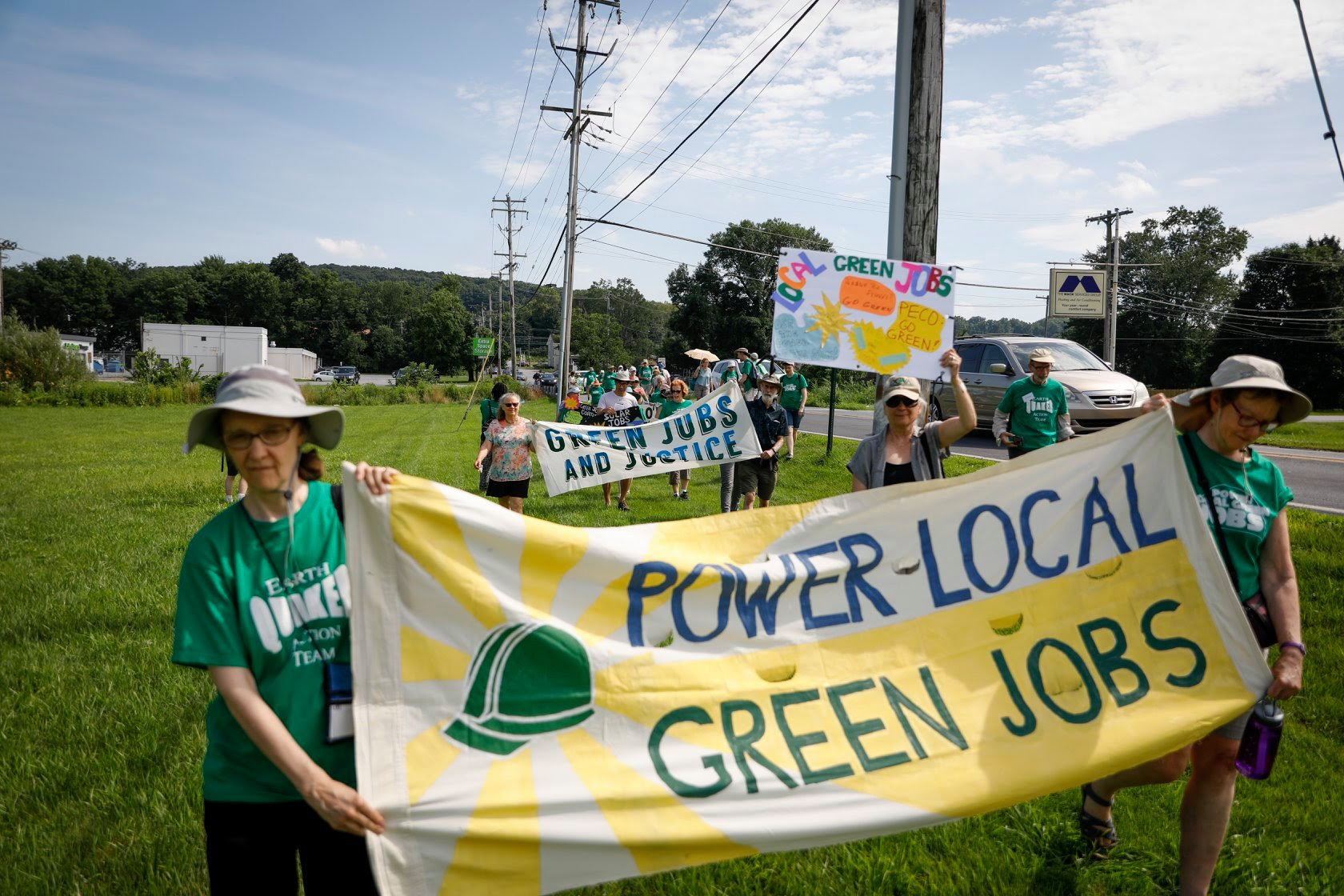 "Marchers carry a banner over green grass alongside a road. Their signs read ""Green Jobs and Justice"" and ""Power Local Green Jobs."""