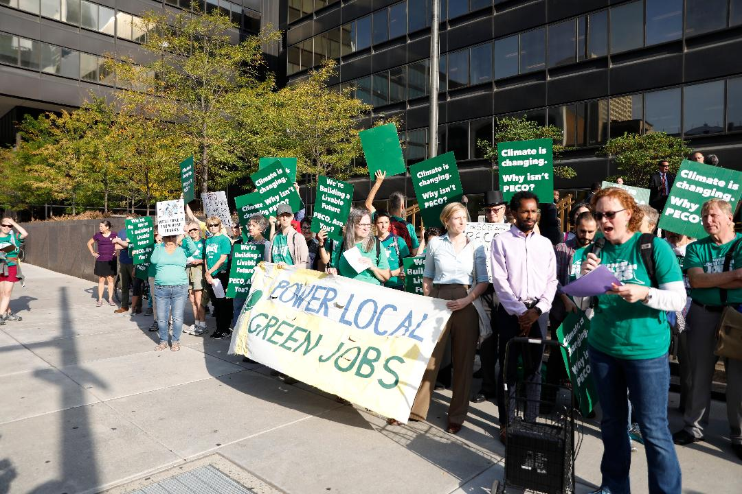 Activists stand with signs and banners in front of the PECO building