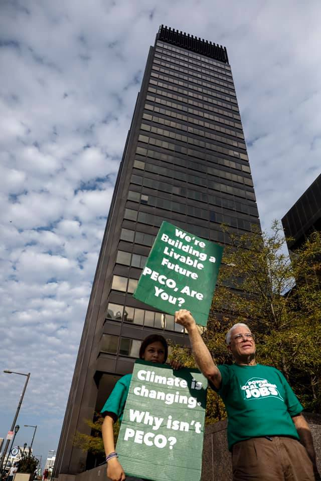 Two activists stand with signs in front of the PECO building