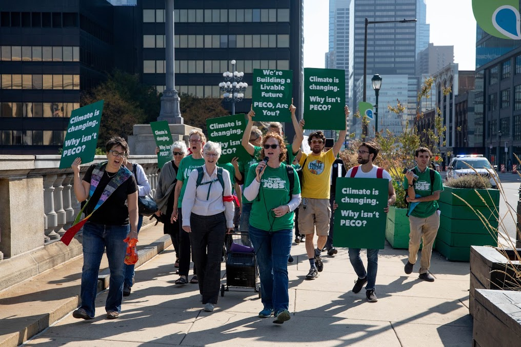 Group of people, mostly wearing green shirts, walk down a sidewalk holding signs and banners