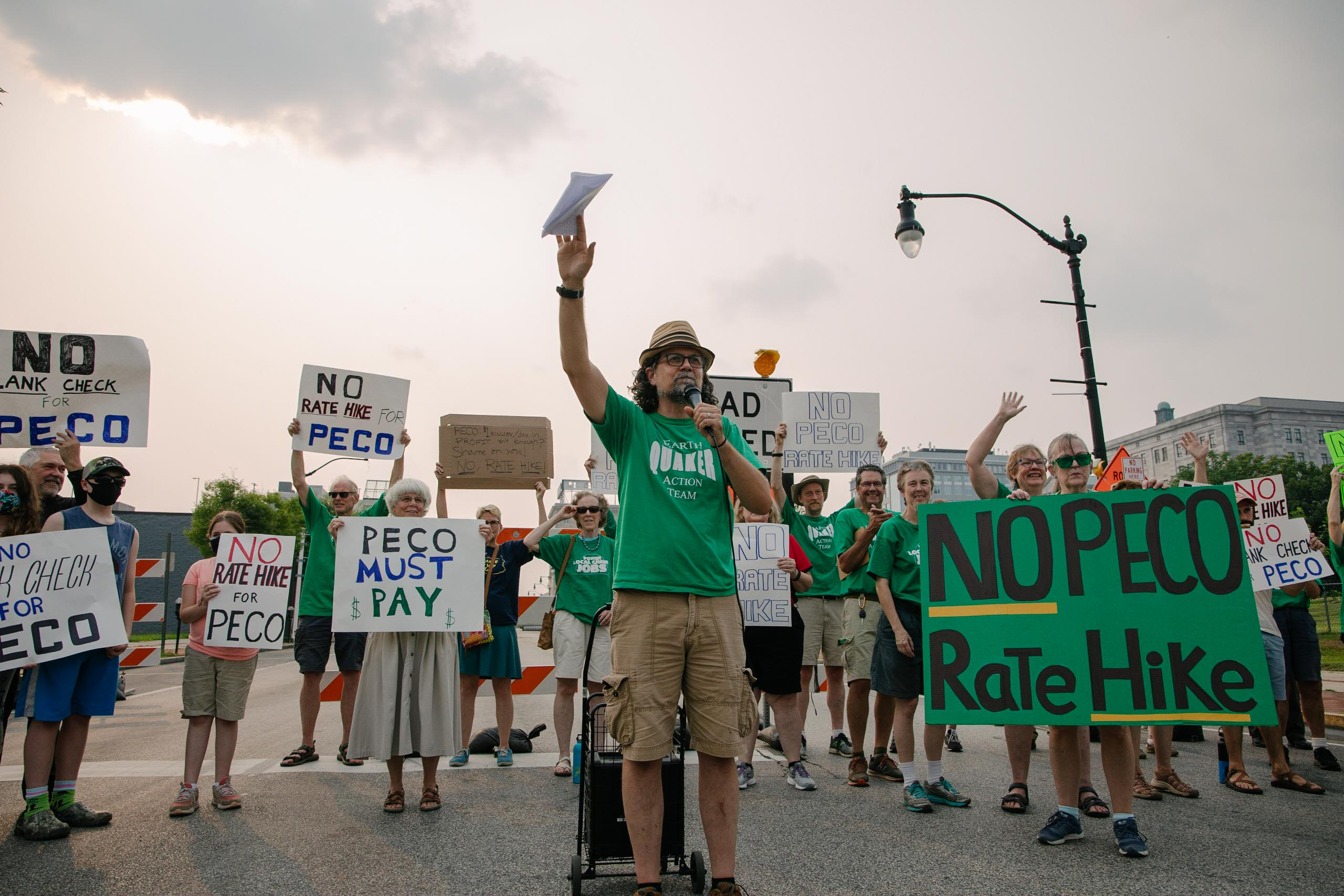 Activists holding signs about PECO's rate hike stand and smile behind an activist wearing a green shirt and speaking into a microphone
