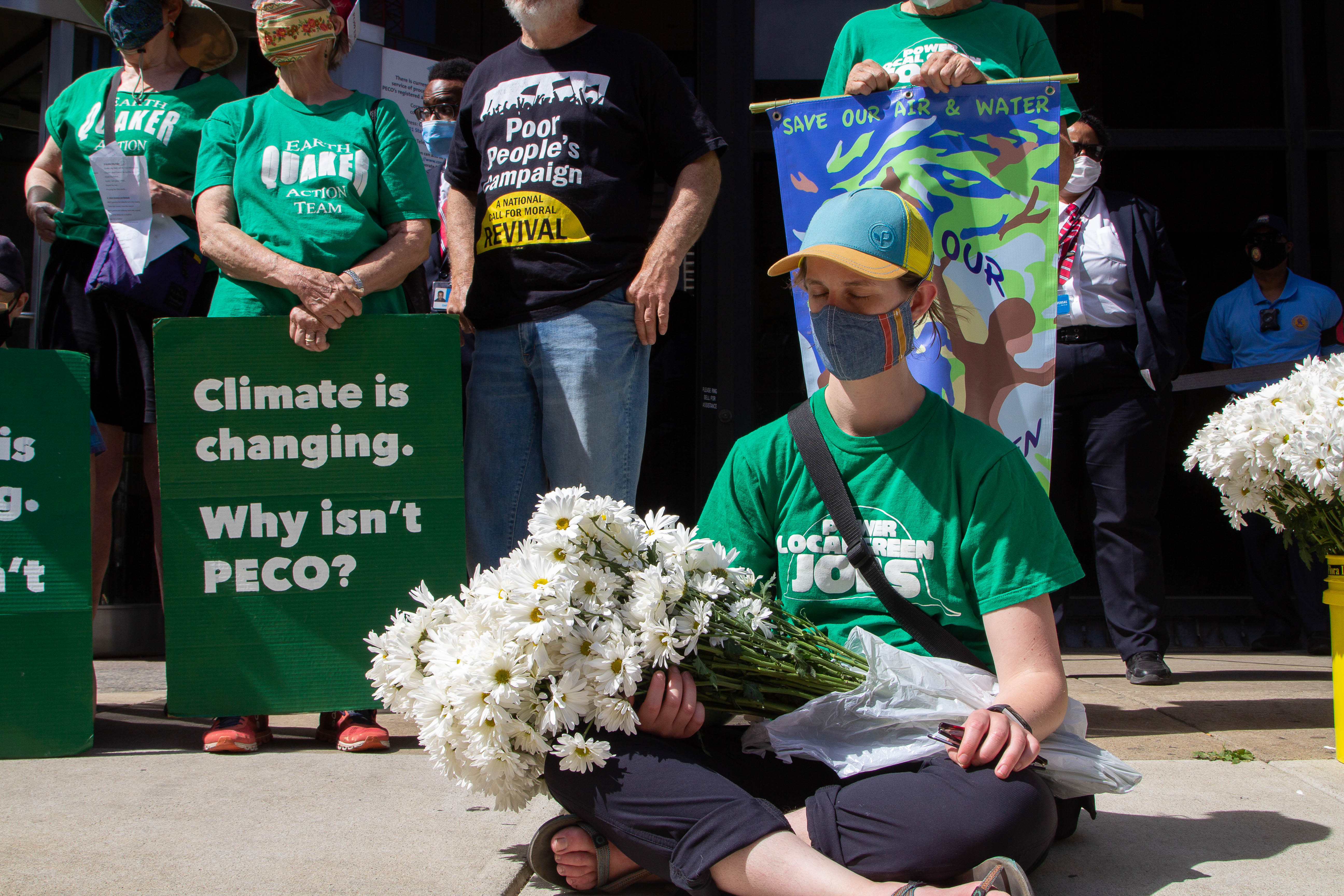 Person holding daises sits cross legged on the ground with eyes closed. People holding signs stand behind.