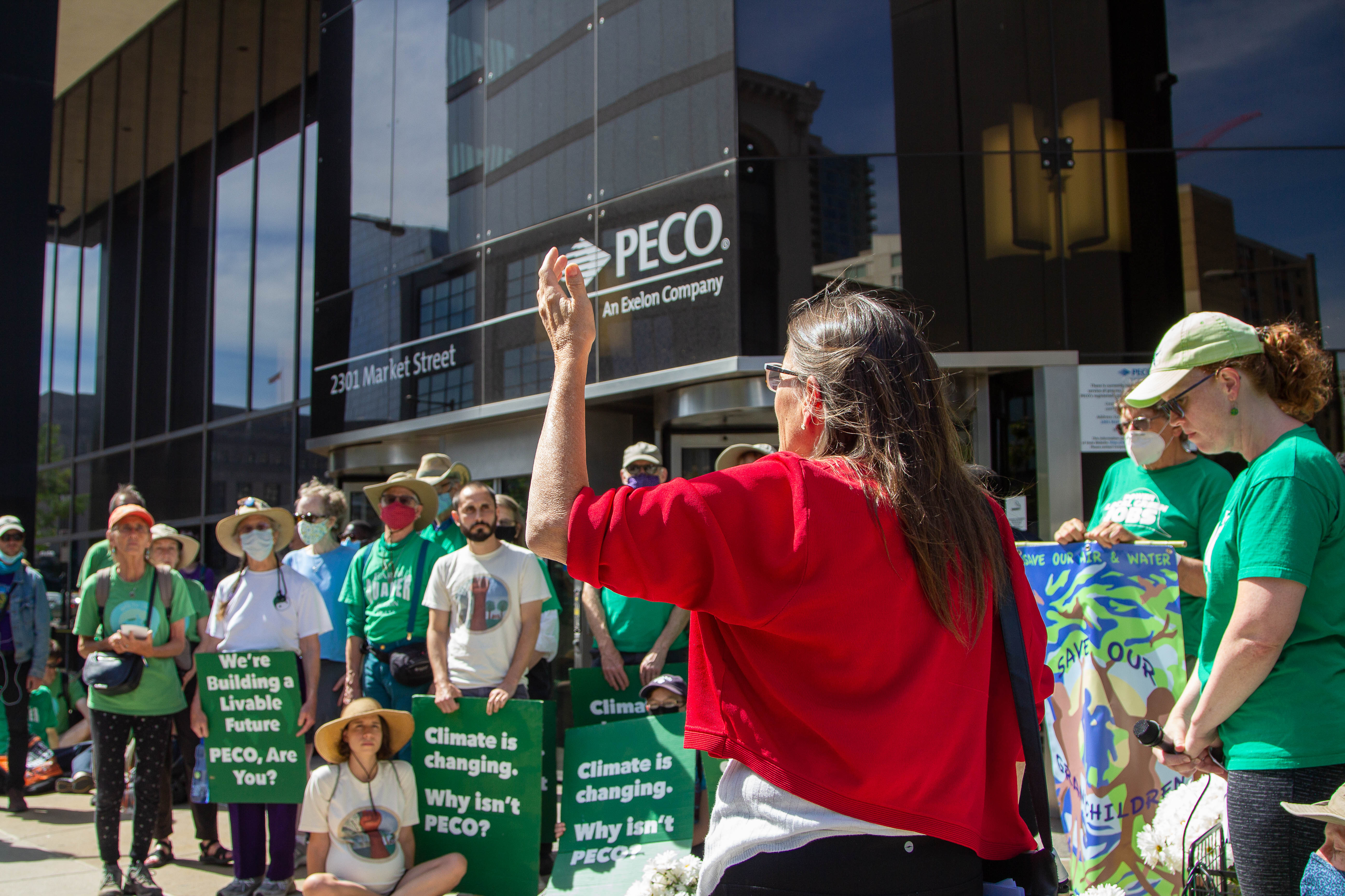 An activist in a red sweater with her back to the camera speaks emphatically to a group of activists gathered in front of PECO's headquarters