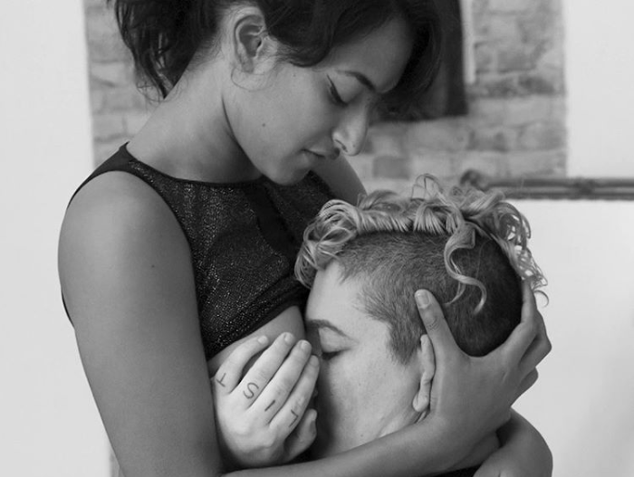 A photo in black and white shows two queer people tenderly embracing. Mahx Capacity rests their face and hands on Kali Sudhra's exposed breasts.