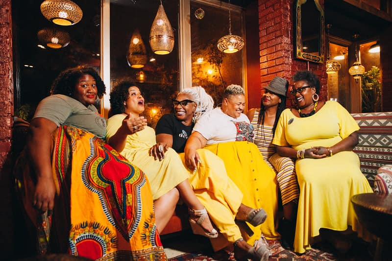 Photo of an event by Decolonizing the Crone. Six 40+ year old Black women of varying body sizes sit together indoors. They are laughing, except the woman on the left who is looking into the camera..