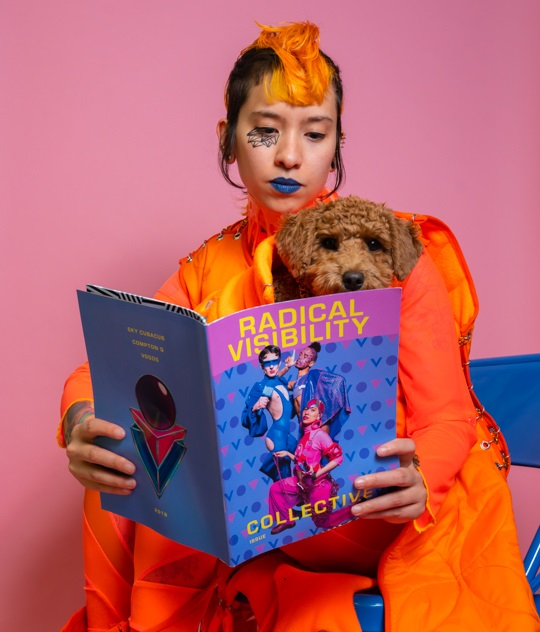 Sky Cubacub is sitting with a dog in their lap, reading Radical Visibility Zine.