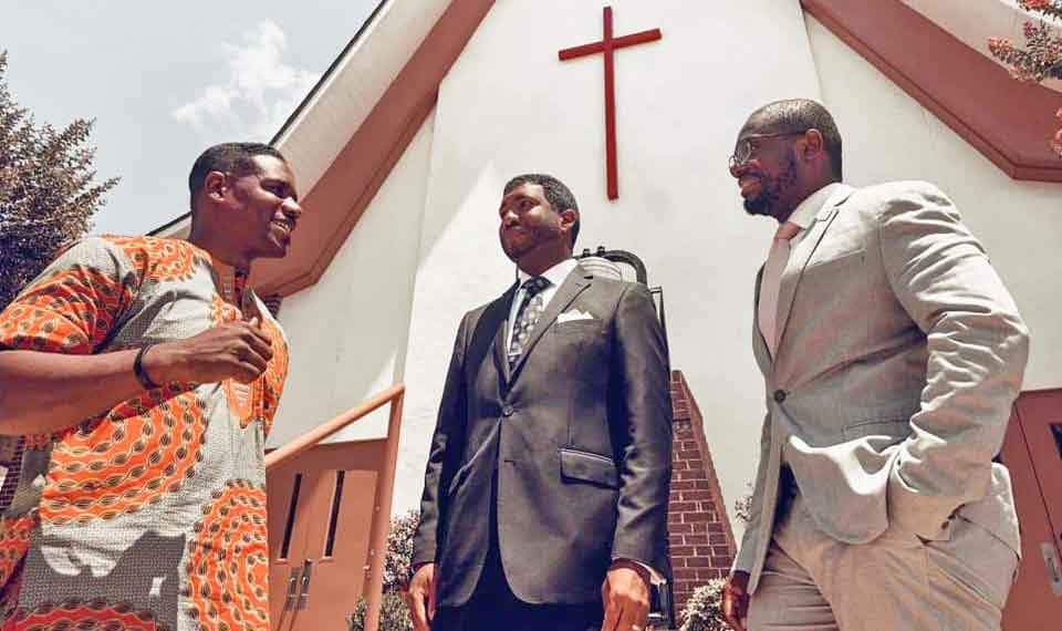 Pastor Chris Butler talking with another minister and a parishioner  in front of a church