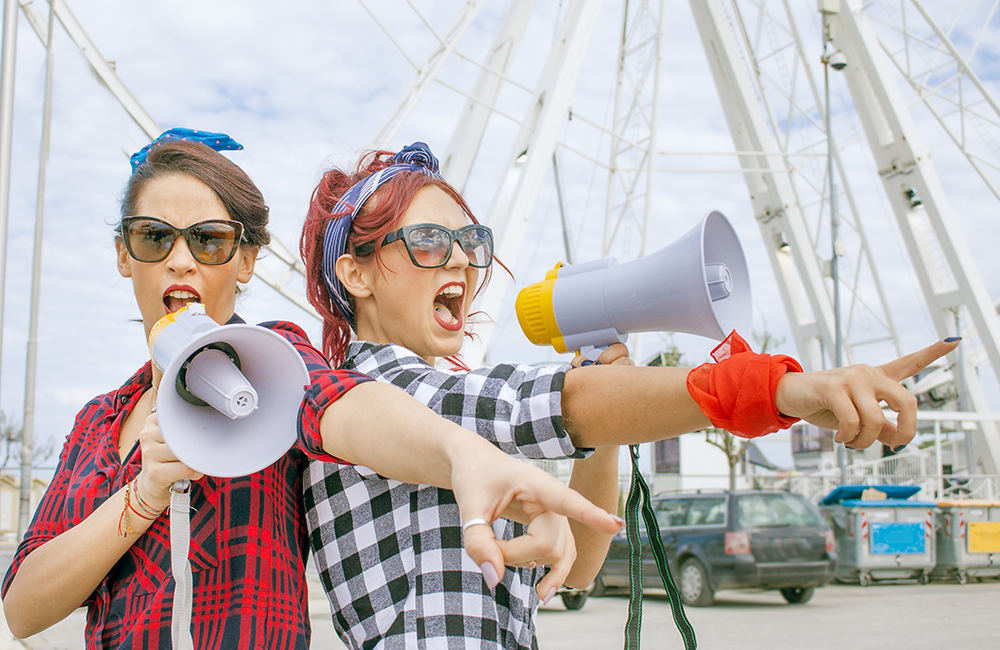Two young women shouting out their cause through a megaphone