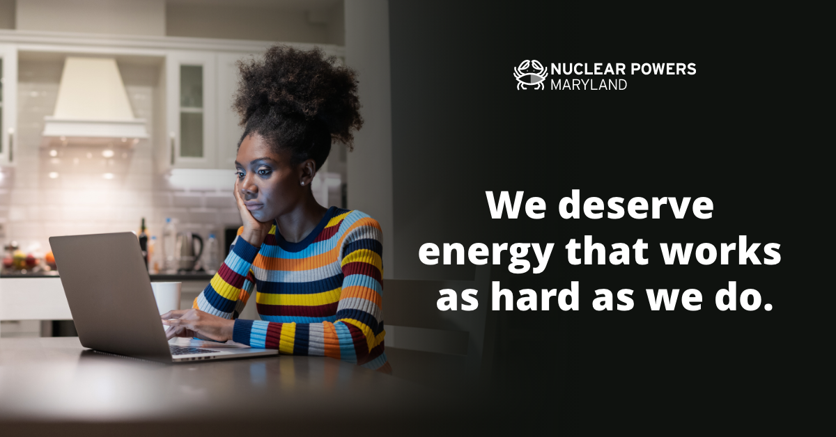 We deserve energy that works as hard as we do text next to woman at laptop