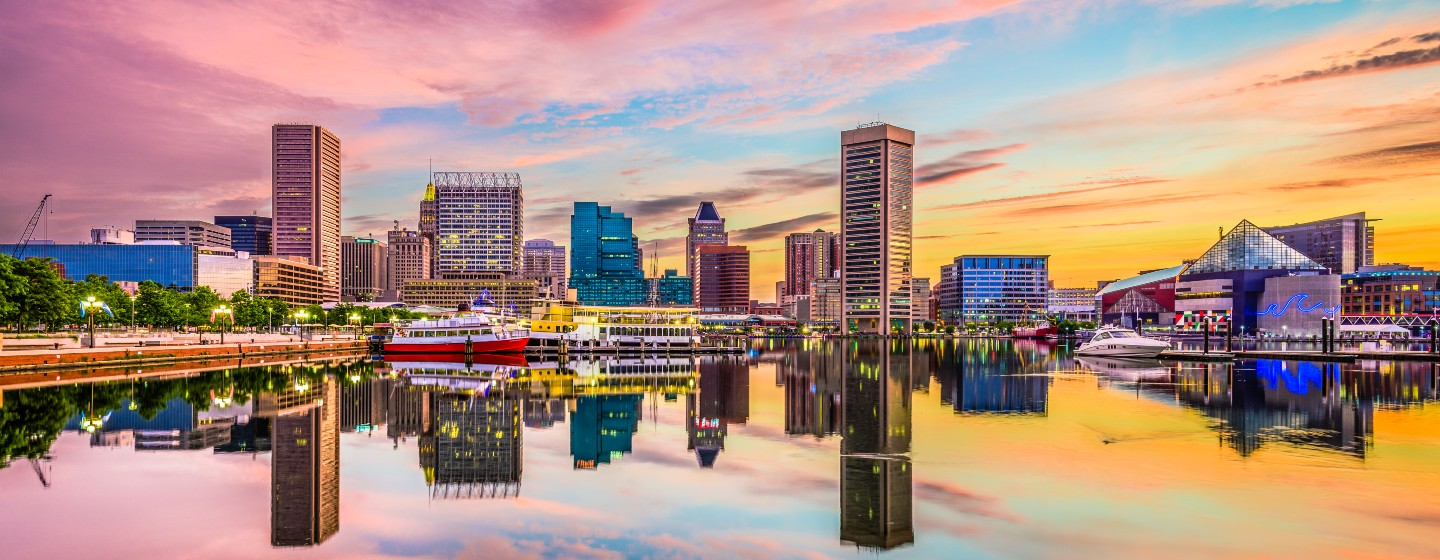 A photo of Baltimore harbor at sunset, with the National Aquarium, other Inner Harbor buildings, and boats lit up and reflecting on the still water