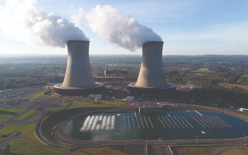 A photograph taken from high altitude of Limerick Generating Station, a nuclear power plant. There is a storage pool of water in front of the plant, which is surrounded by rolling Pennsylvania countryside