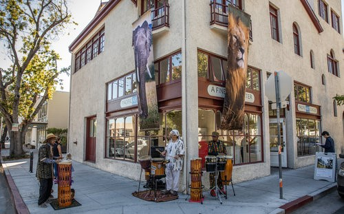 A street corner with musicians playing drums in front of the Pacific Arts League's building.