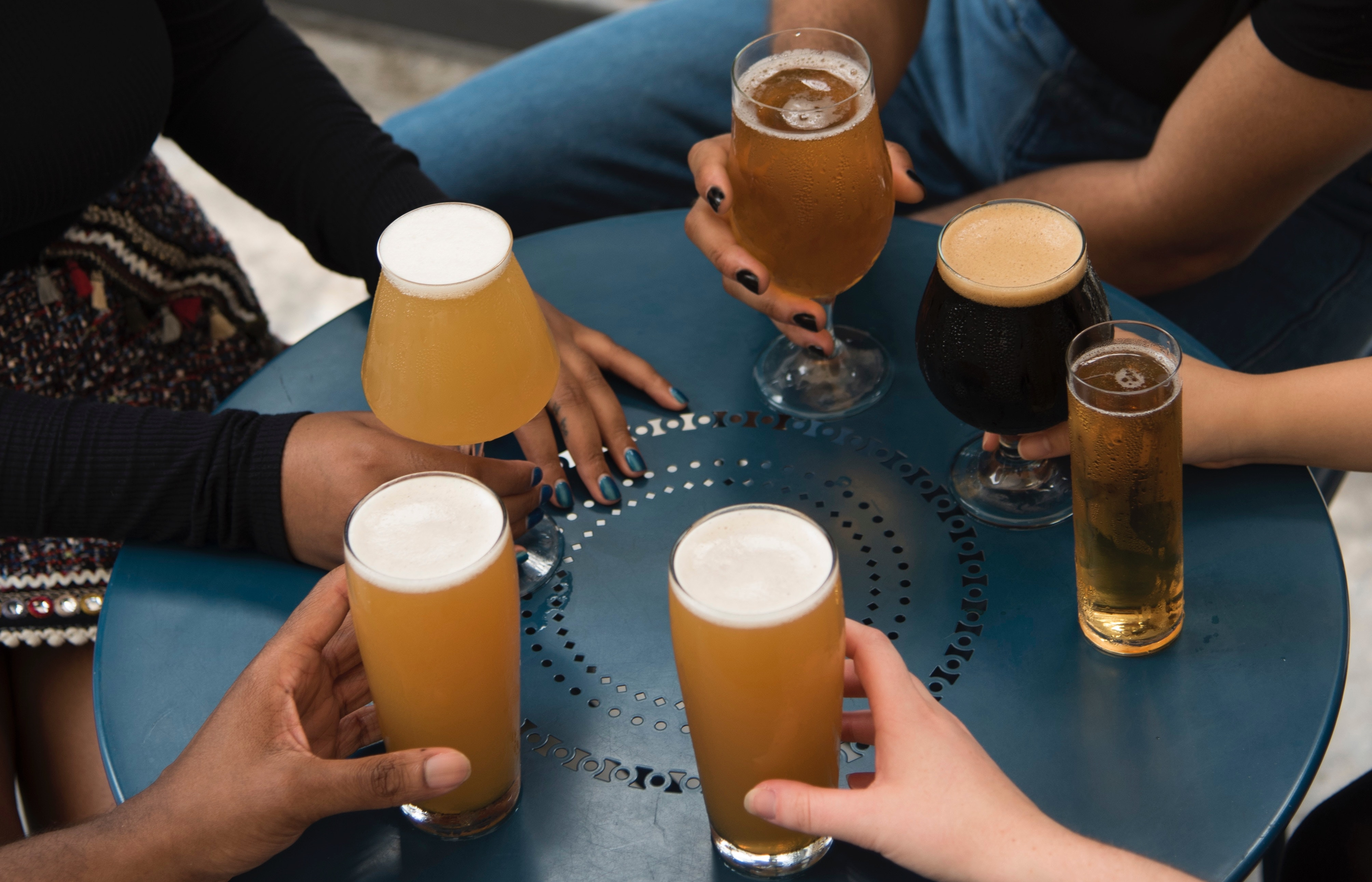 Several people's hands holding beer glasses in a circle on a small table.