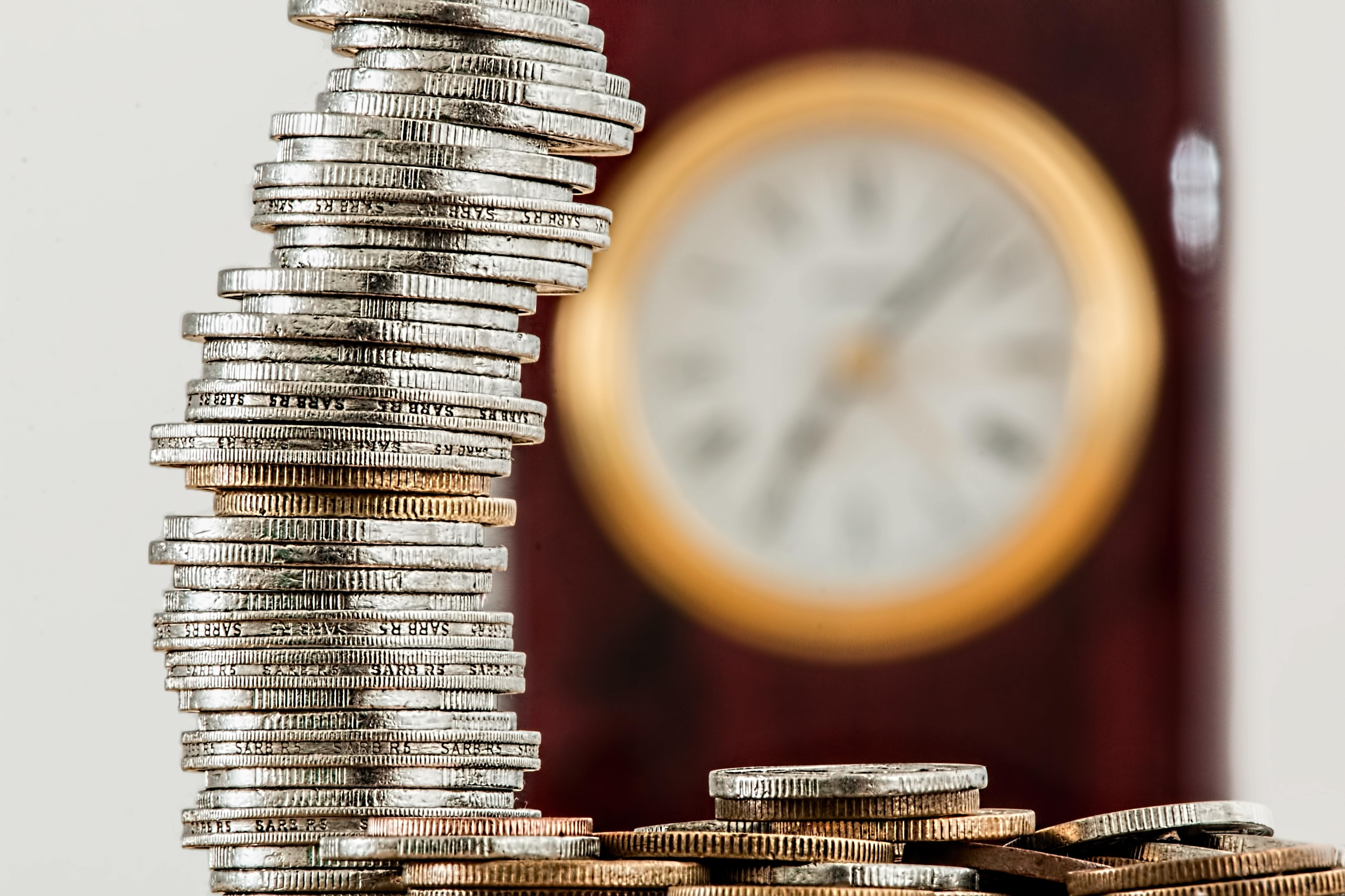 A pile of coins with a clock in the background signifying that time is ticking for debt relief