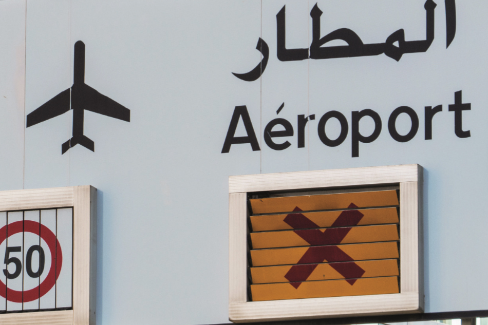"Close up of a road sign directing traffic to the airport. Features the word ""airport"" written in Arabic and French."