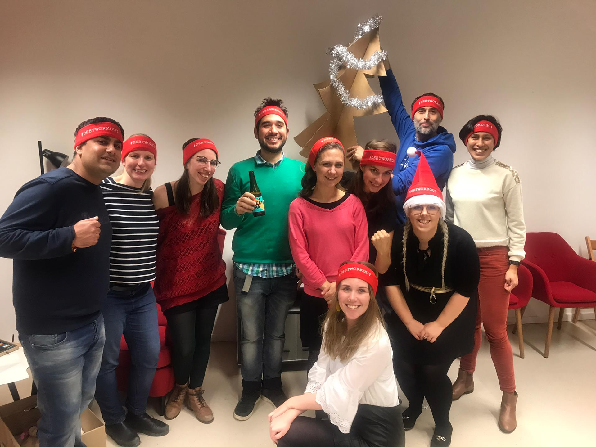 The Eurodad team at Christmas wearing Debt Workout headbands and holding up a cardboard christmas tree decorated in gold tinsel