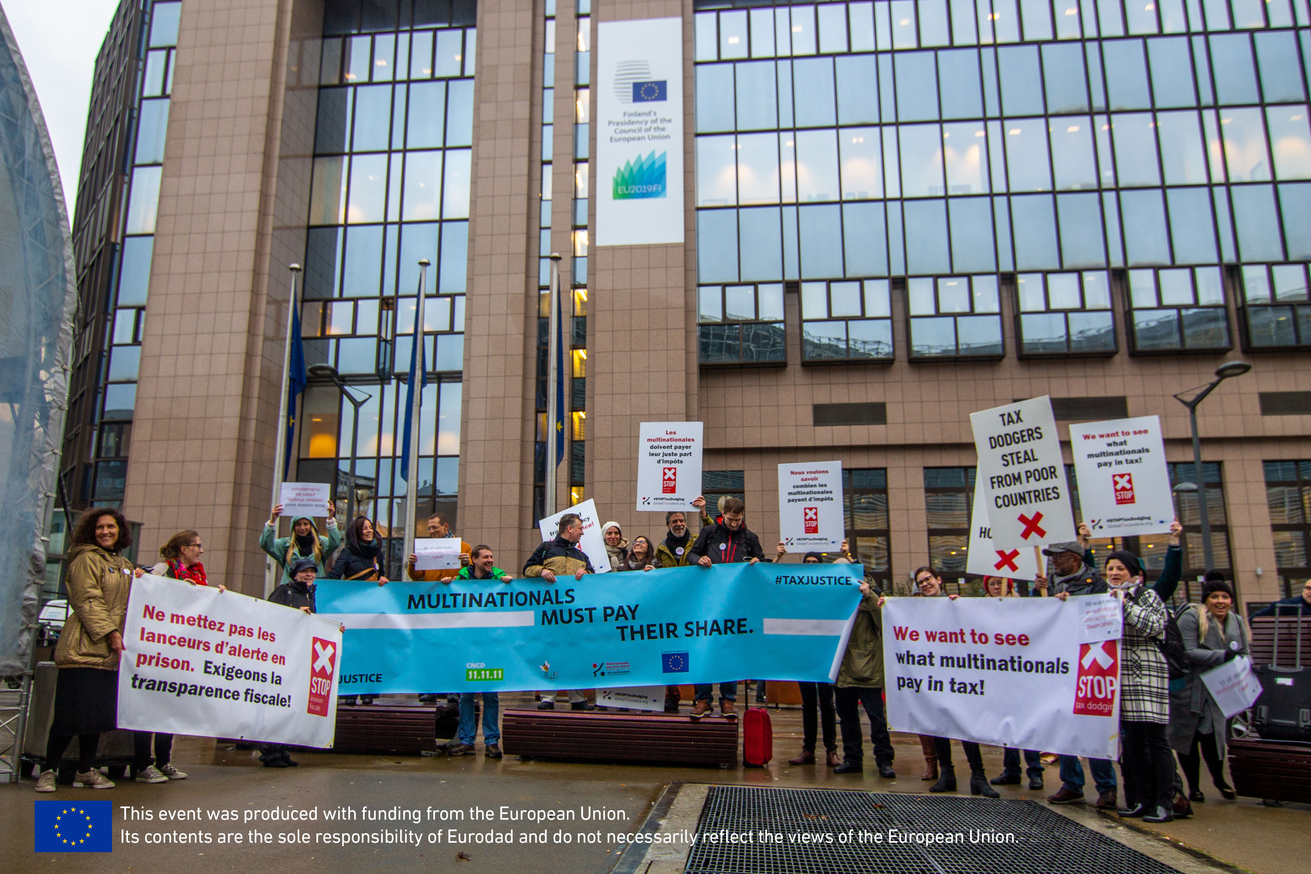 Eurodad and other Brussels-based CSOs stand in front of the European Commission HQ holding placards calling for tax transparency and that mulitnational corporations pay their share.