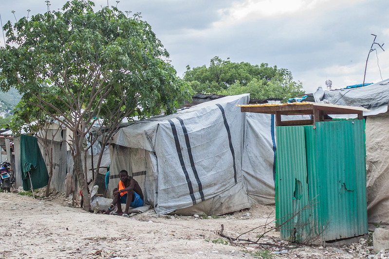 A man sits outside a temporary shelter in Delmas camp for people internally displaced by the 2010 Haitian earthquake