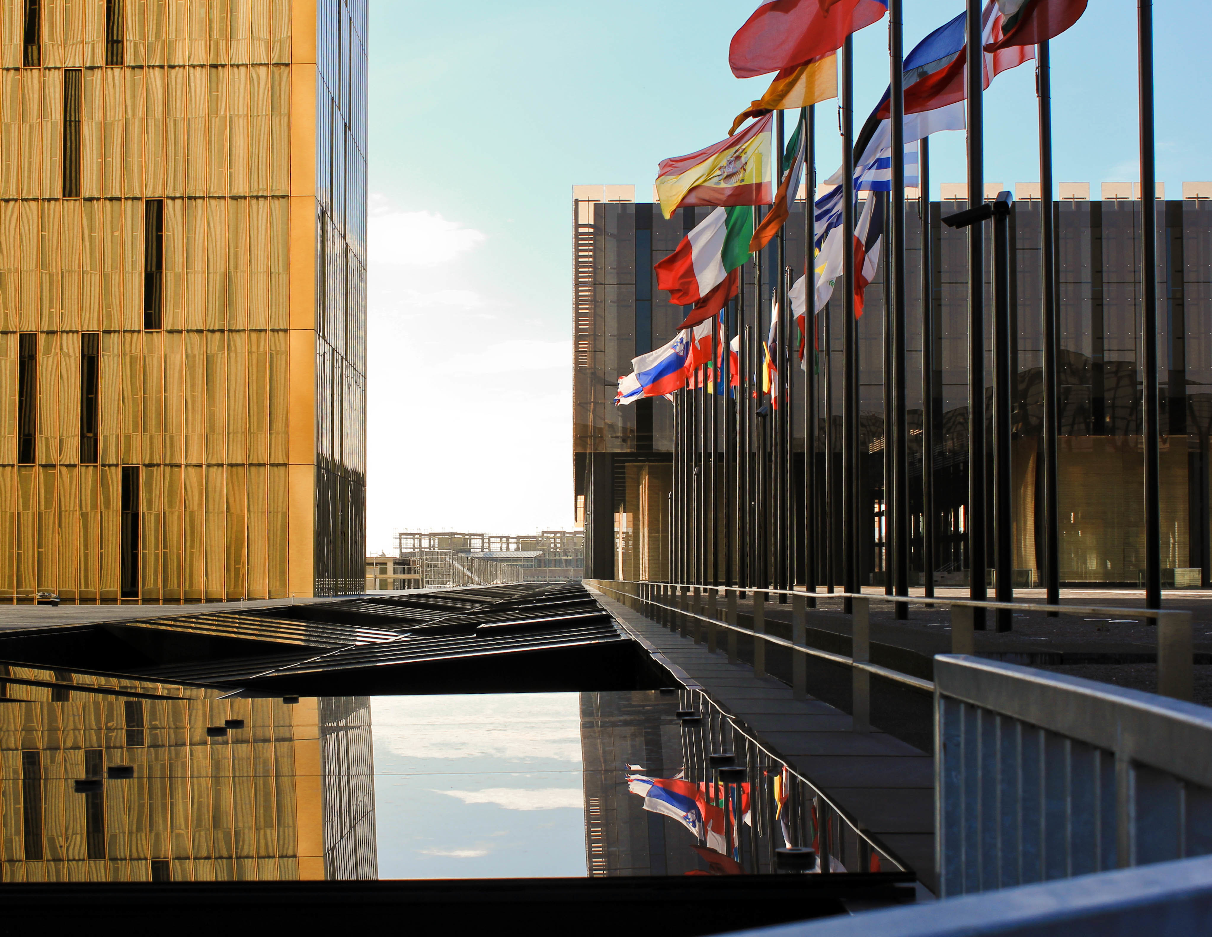 Flags from EU member states fly outside the European Court in Luxembourg, reflected in the water surrounding the building