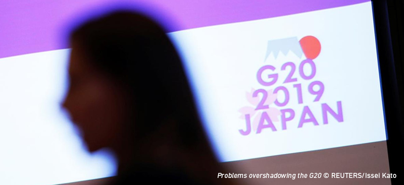 "A woman in silhouette walks past a bright TV screen reading ""G20 2019 Japan"""