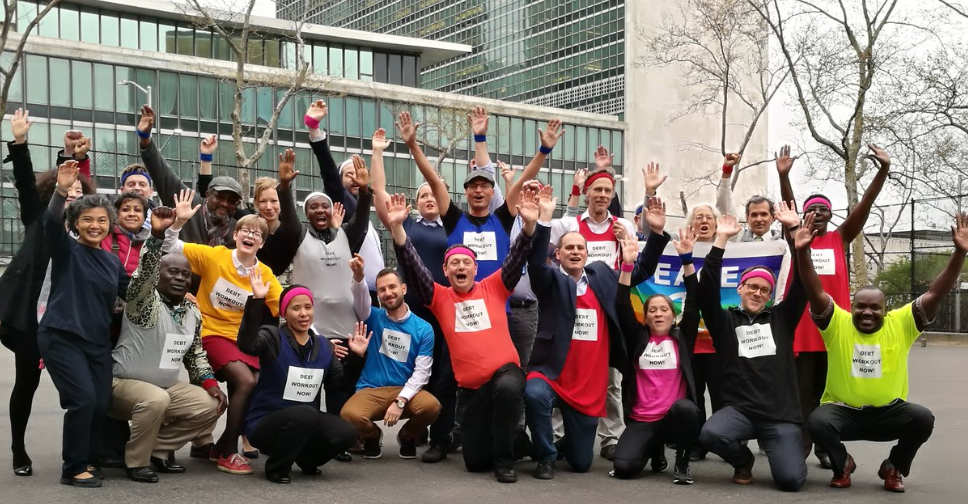 "CSO activists dressed in 1980s-style sports gear outside the UN HQ in New York. Their tshirts read ""Debt Workout Now"""