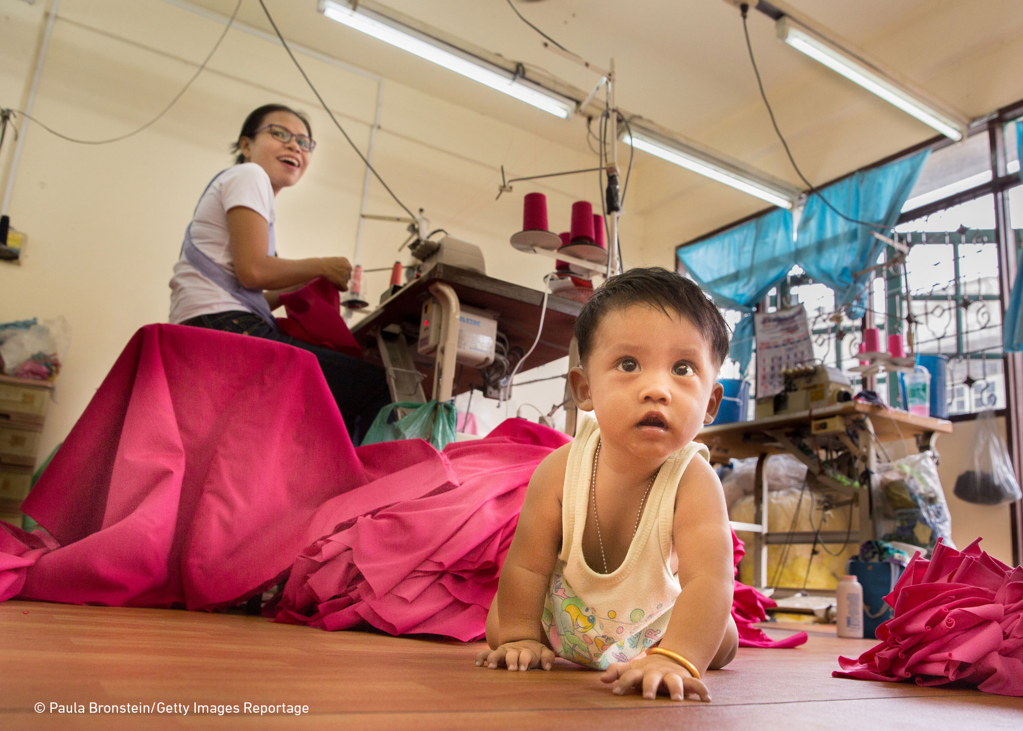 A toddler crawls to the camera as his mother sews garments behind him. Dominant colour - hot pink from the swathes of cloth which separate the child from their mother.