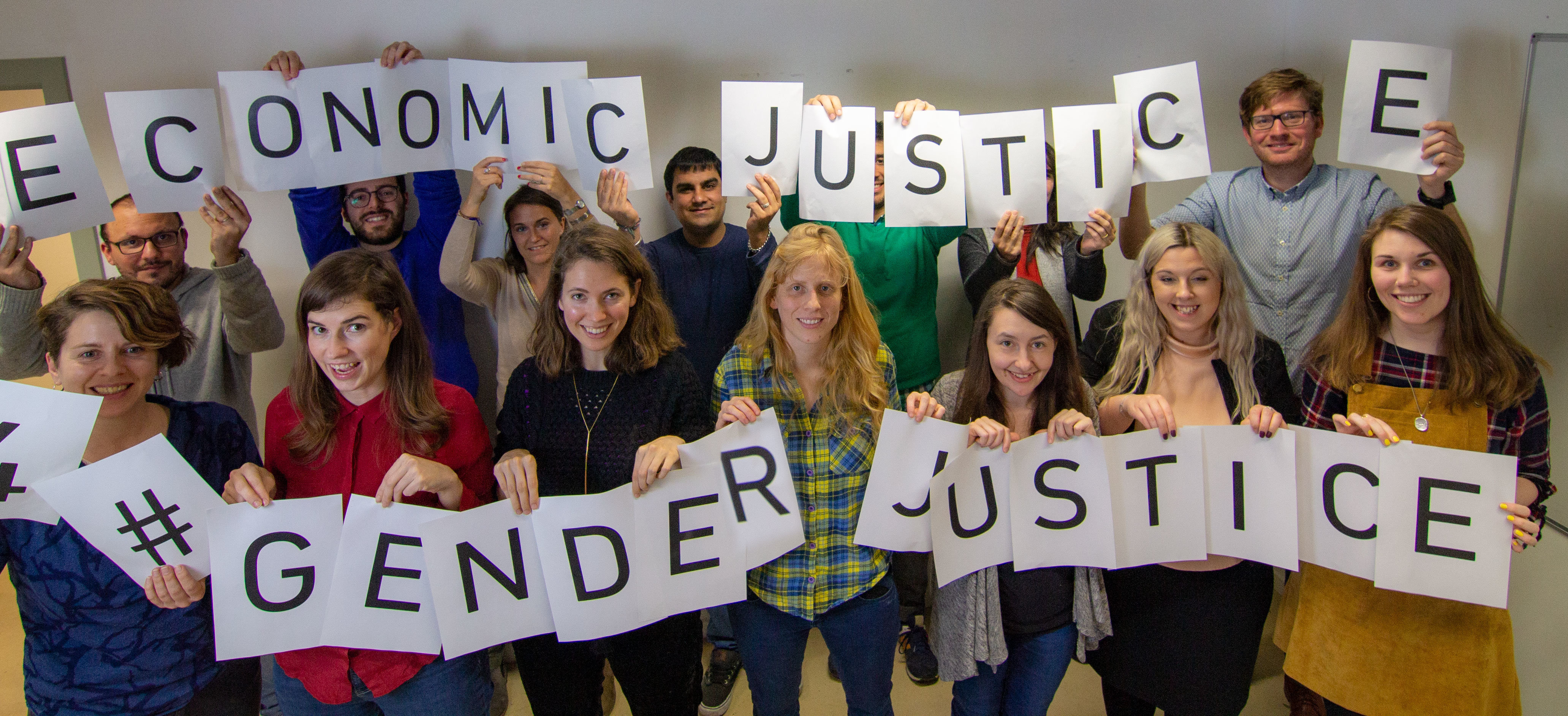 "Eurodad, Fern and Saferworld staff celebrating International Women's Day 2019 holding printed letters reading ""Economic Justice 4 Gender Justice"""