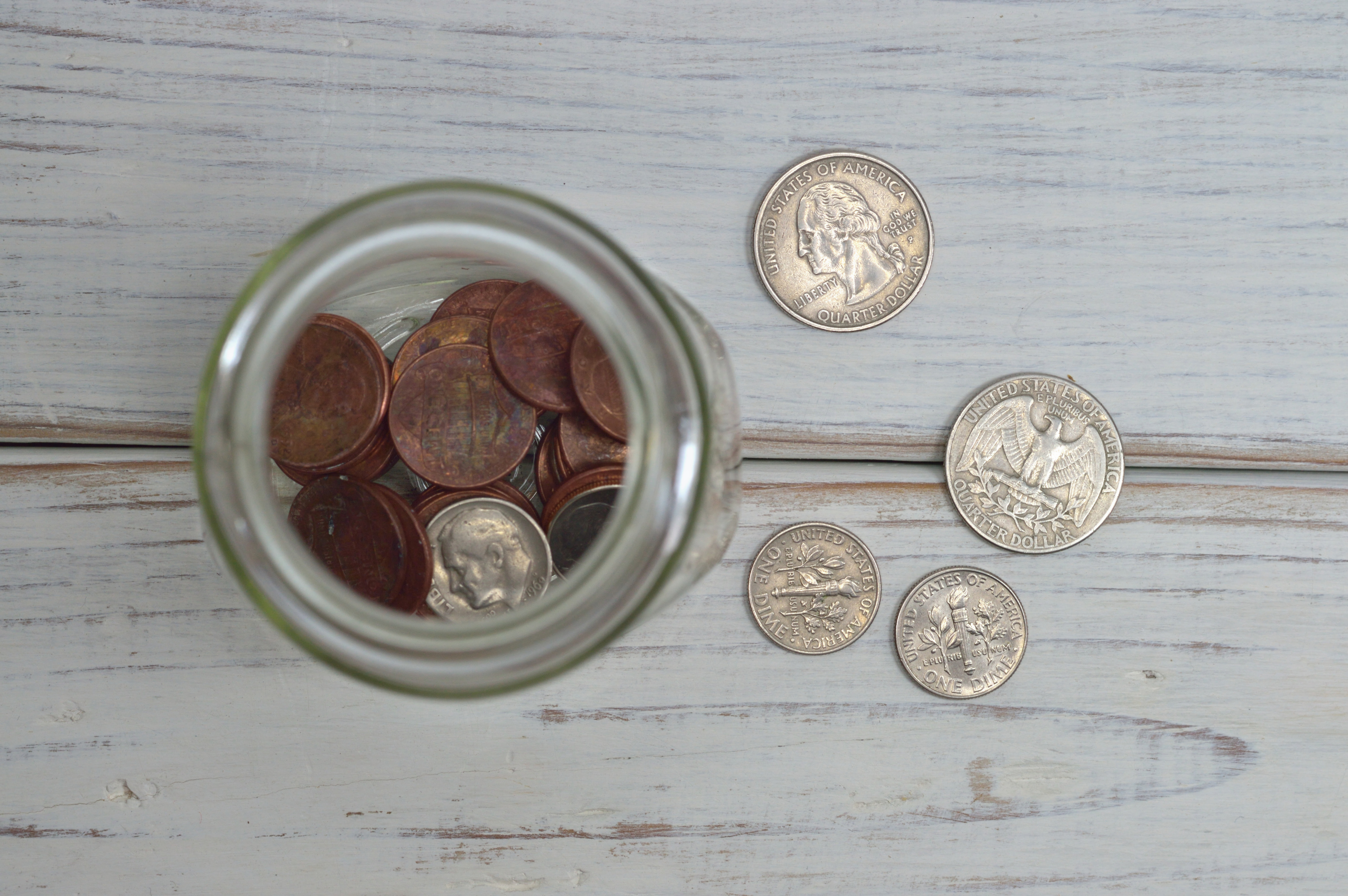 A jar of quarters and US pennies sit on a wooden table