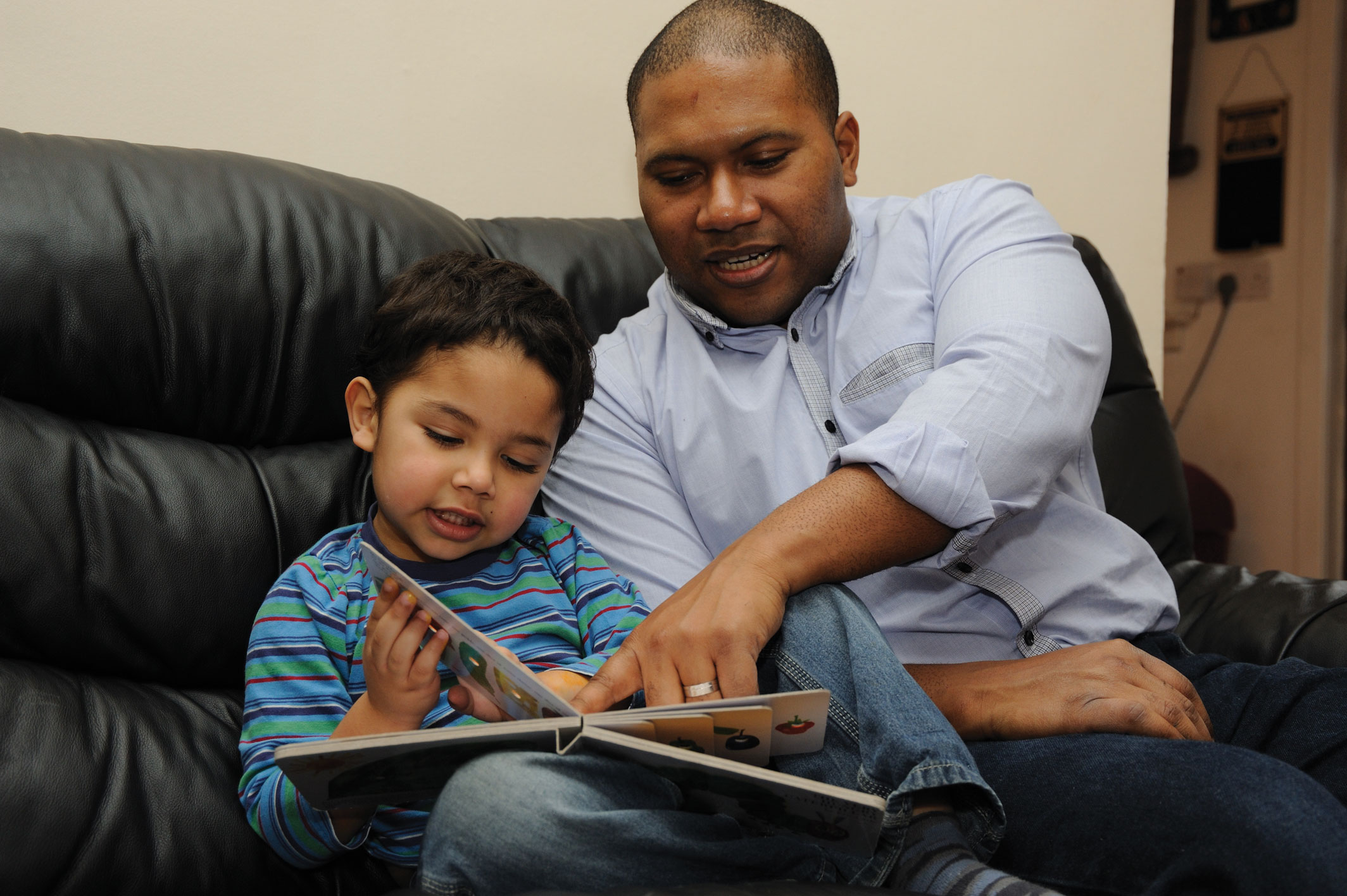 A dad reads with his son - NHS images
