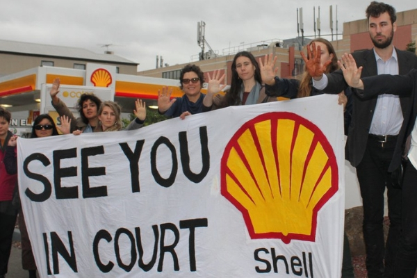 Protest at Shell petrol station with banner: See you in court, Shell!