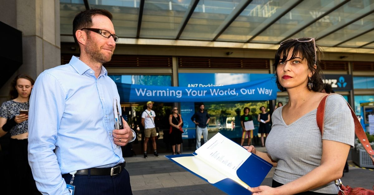 ANZ representative ben Walker receives the complaint from Friends of the Earth's legal officer Emila Nazari