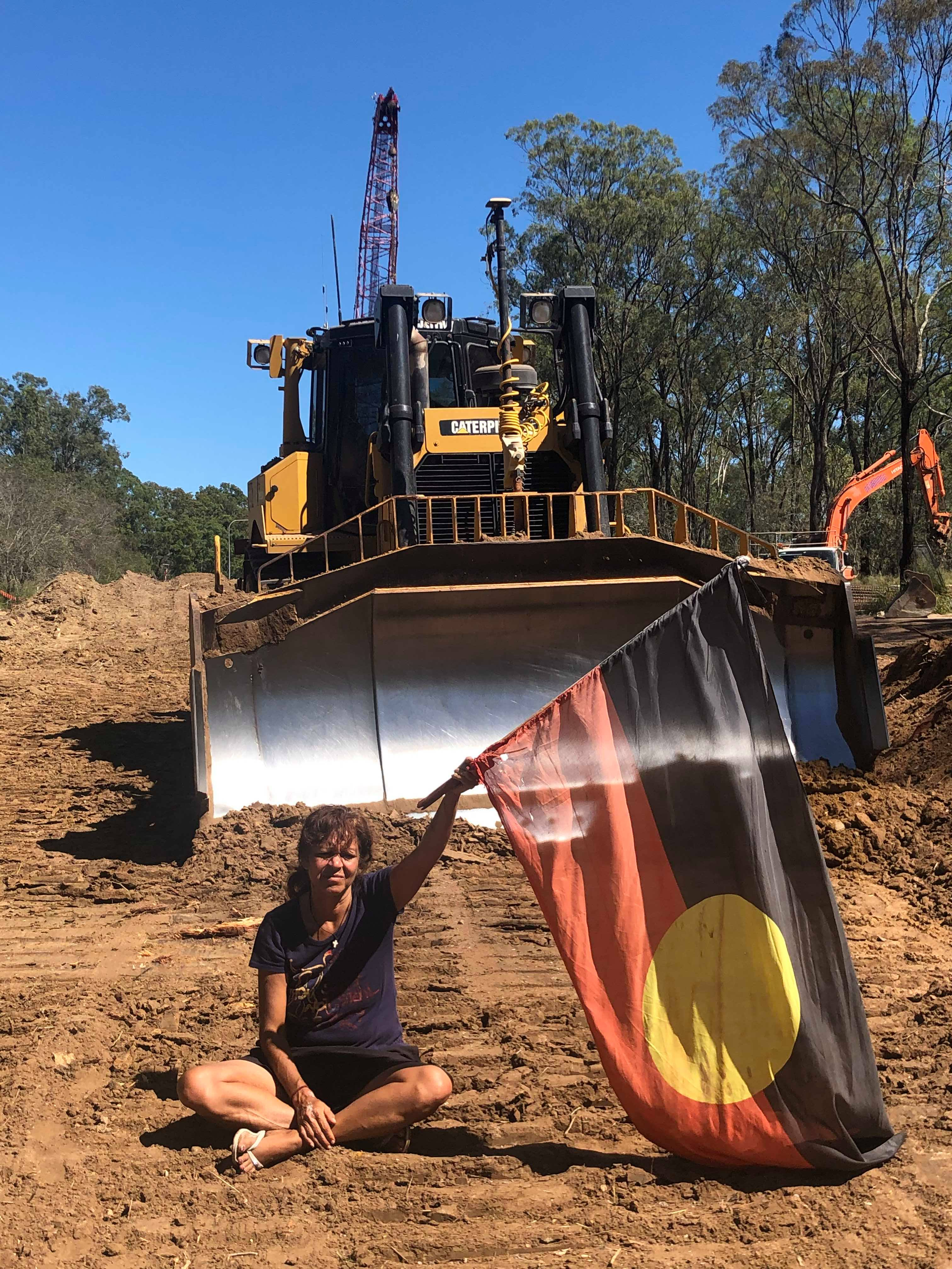 Image: Goori Sovereign Land Council - Woman with Aborignal flag sits in protest in front of a bulldozer