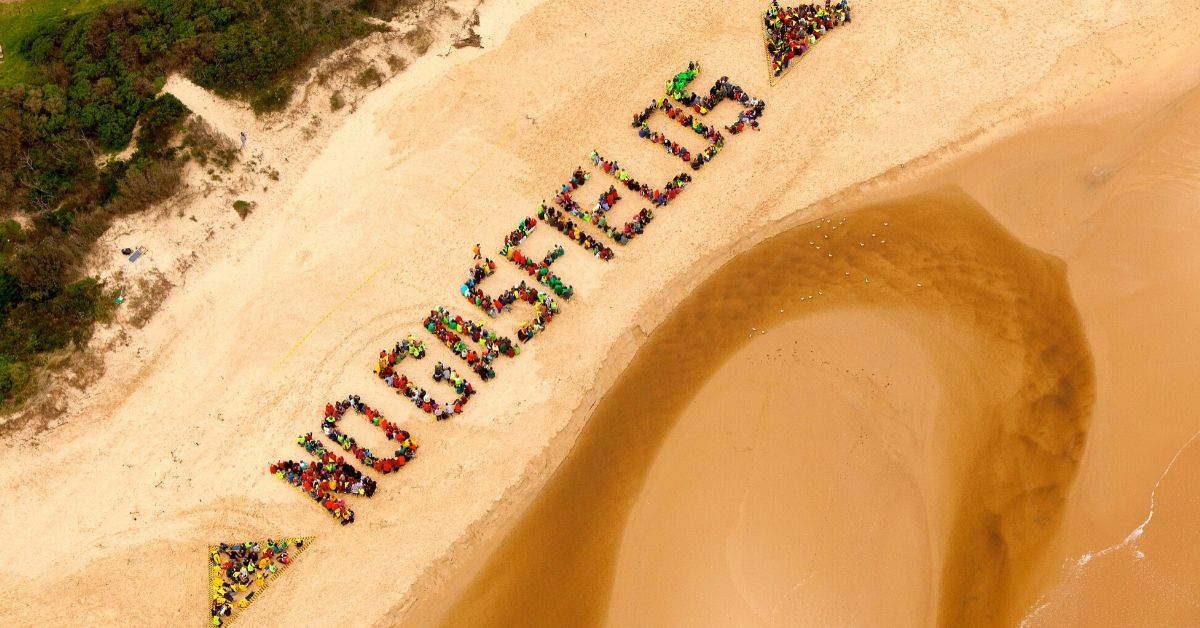 Community protest at beach in giant human sign